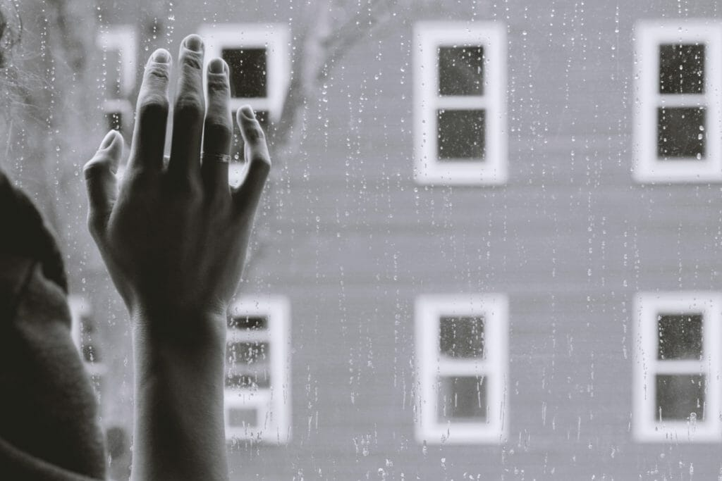窓に手を置く女性