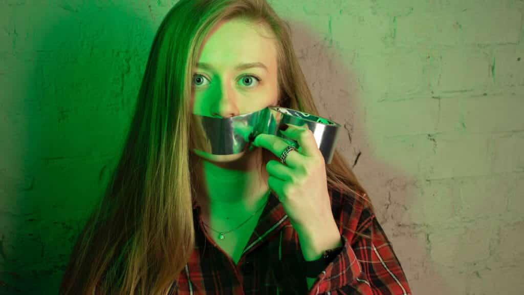 口にテープを張る女性