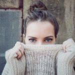 セーターを鼻まで上げた女性